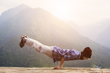 Tourist man traveling in Himalayas mountains doing morning yoga exercise