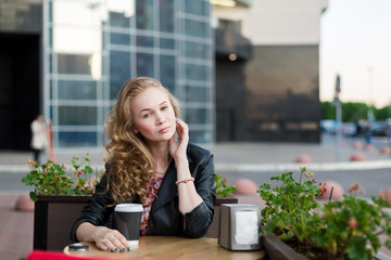 Beautiful blonde girl in dress and black leather jacket sitting in a cafe at a wooden table on the summer terrace on the background of the business center, and drinks coffee from a plastic cup.