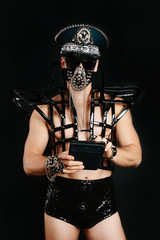 Man in black  sexy costume mask and cap with metal elements on black background using tablet pc