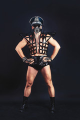 Studio portrait of Dancer Man in black  sexy costume mask and cap with metal elements on black background