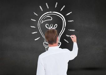 Man drawing a light bulb on blackboard