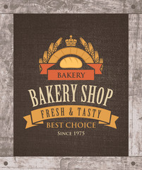 Vector banner for a bakery shop with a picture of the loaf and ears of wheat on the background of sacking and in wooden frame.