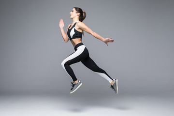 Side view of a sporty young woman jumping isolated on grey background
