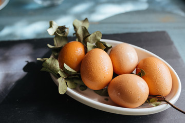 Farm eggs nestled in a bowl on leaves on blue wooden table