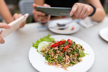 People taking photo on food with mobile phone