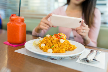 Woman taking photo on fried noodles with cellphone