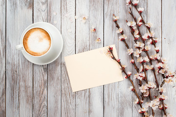 cup of coffee next to spring white flowers on wooden texture