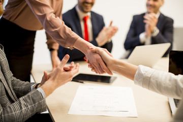 Business people shaking hands  finishing up a meeting in office