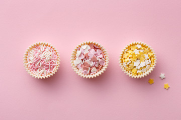 Flat lay of colorful sprinkles on a pink background. Top view of cake decoration