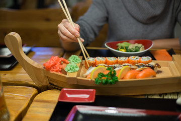 Arms of woman take sushi and other food  in japanese restuarant