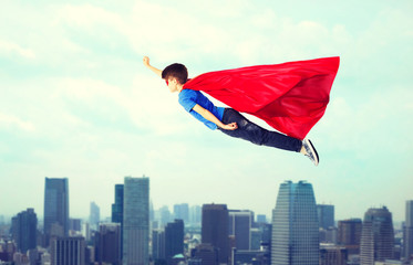 boy in red superhero cape and mask flying on air