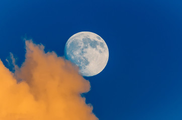 Full moon peeking out from behind the clouds, sunset sky