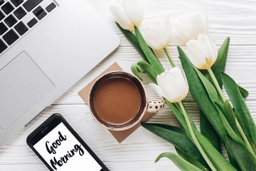 good morning text sign on phone screen and laptop with morning coffee and tulips on white wooden rustic background. stylish flat lay with flowers and working gadgets. freelance. home working