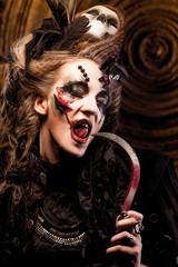 Young  witch hloding sickle. Bright make up, skull, smoke-  halloween theme.