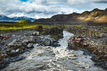 Travel to Iceland. Beautiful Icelandic landscape with river, mountains, sky and clouds. Trekking in national park Landmannalaugar. Mountain river in Iceland.