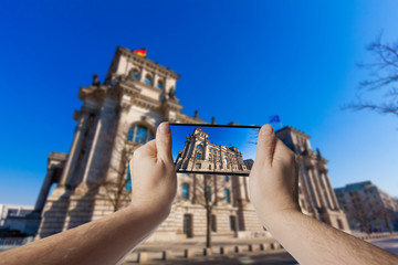 Hand with smartphone taken pictures of The Reichstag building in Berlin, Germany