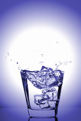 Ice cubes splashing into glass, ice cube dropped into glass of water, fresh, cold water, isolated on blue background.
