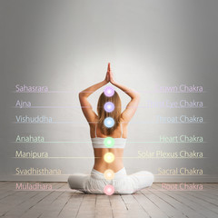Young and healthy girl meditating in lotus position. Colored chakra lights over her body. Yoga, zen, Buddhism, recovery, healthcare and wellbeing concept.