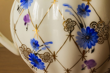 Porcelain sugar bowl with golden pattern and blue flowers. Close-up. Hand-painted old sets. Imperial Porcelain Factory..
