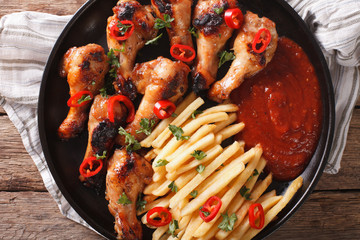 Grilled chicken wings with french fries and ketchup close-up. Horizontal top view