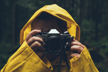 Person in yellow raincoat using camera