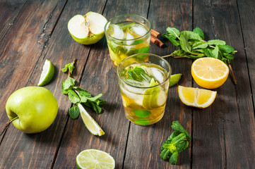 homemade lemonade with lime, mint in a glass on a wooden rustic table