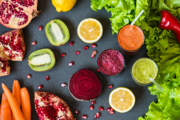 three glasses of different fresh juice. Beet, carrot and kiwi juices on grey background