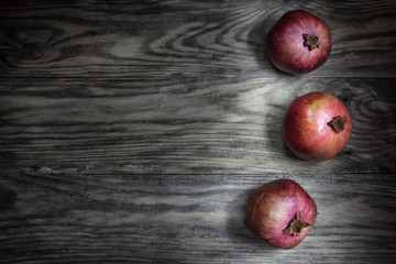 Three large red pomegranate are on a rustic table. Composition for design recipe or menu.