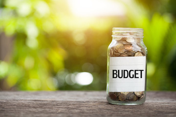 BUDGET word with coin in glass jar with Savings and financial investment concept.