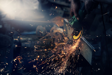 Local worker grinding,sparks during working with grinder in the old factory.Real situation picture and color toned.