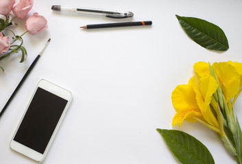 White paper background with flowers and leaves. Designer workplace with smartphone.