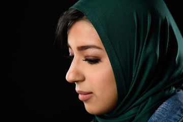 Portrait of a beautiful Muslim woman dressed in hijab on a black background in photo studio.