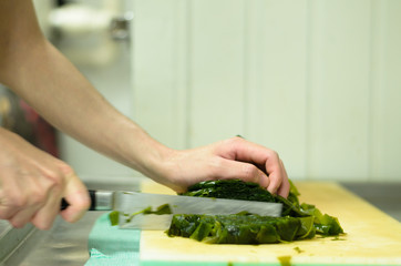 Chef cutting seaweed prepare food in restaurant,Hand cutting vegetable fast it's skill