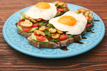 Sandwich with egg, tomato, greens, and mushrooms