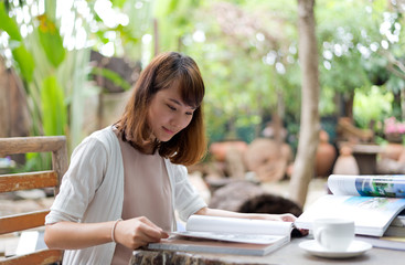 Young woman reading magazine with cofee break in garden on summer day, select focus