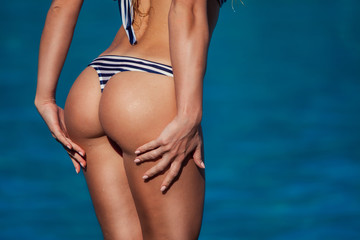 An athletic girl shows her butt in a bikini at a close distance.