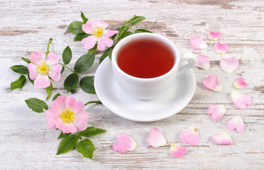 Cup of tea and wild rose flower on old rustic wooden background