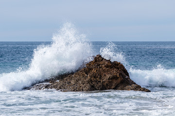 Wave breaking on a rock just offshore, sending sea spray flying into the air. Located in Crystal Cove State Park in Laguna Beach, California.