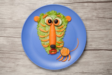 Astonished tiger made of salad and carrot on plate and table
