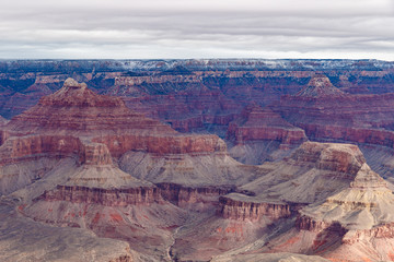 Panoramic view of the Grand Canyon in winter, portraying the colorful formations of the canyon's north side. The top edge of the canyon sports a thin stripe of snow from the just concluded storm.