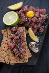 Tuna tartar with black and white sesame, quail egg yolk and slices of bread, close-up