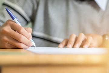 students hand holding pen fill in Exam carbon paper sheet or test paper on wood desk