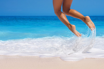 woman legs, jumping on the beach, with dynamic motion blur