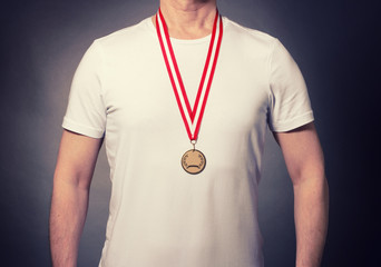 An athlete with a medal around his neck on a dark background.