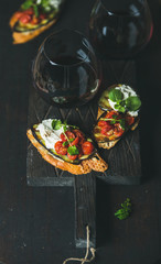 Wine and snack set. Brushetta with roasted eggplant, cherry tomatoes, garlic, cream cheese, arugula and glass of red wine on wooden board over dark background, selective focus. Slow food concept
