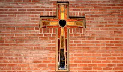 beautiful stained glass cross set into a brick wall.