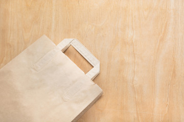 Clean brown kraft paper bag lying on a plywood table. Mock up.