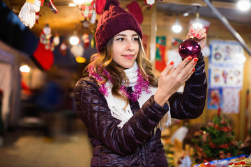 Beautiful  girl choosing Christmas decoration