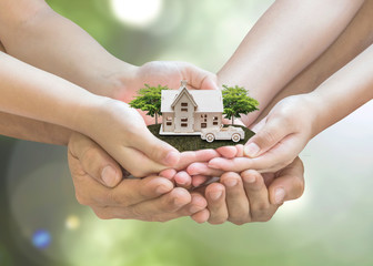 Safe family house model and garden on son daughter children kid guardian mother father hands, blur natural greenery tree planting environment background: Home loan property ownership assurance concept