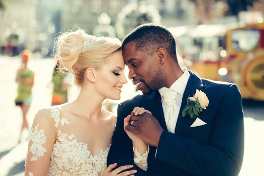 Loving couple of cute bride and african American groom